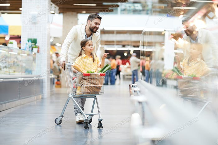 Cute girl helping father with shopping in supermarket
