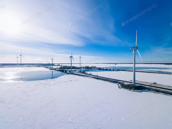 Luftaufnahme von Windmühlen mit blau gefrorenen Fluss im Schnee Winter Finnland.