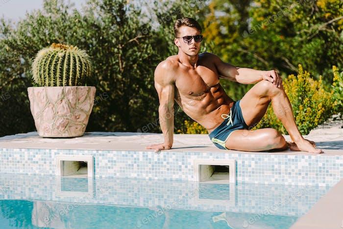 Sexy muskulösen Mann in Badehose entspannen und posieren in der Nähe von Schwimmbad im Freien