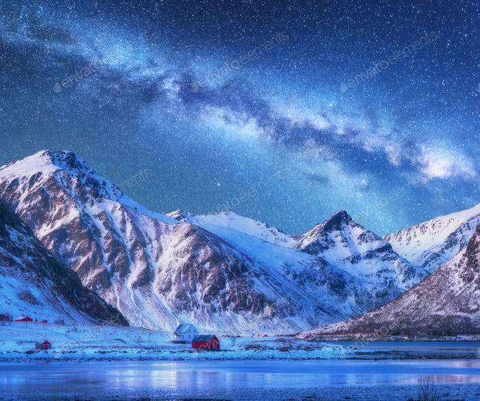 Milky Way above houses and snow covered mountains in winter