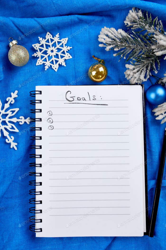 Top view of blank notebook for goals resolutions and christmas decoration