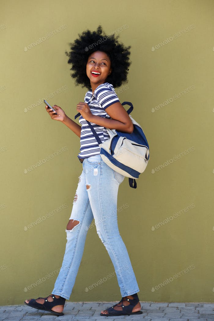 beautiful happy woman walking with bag and smart phone