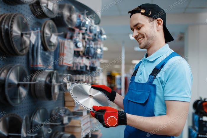 Male worker choosing disc for saw in tool store