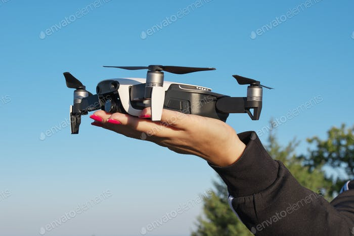 Drone landing on a woman hand