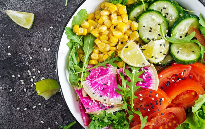 Bowl with fresh raw vegetables - cucumber, tomato, watermelon radish, lettuce, arugula and corn.