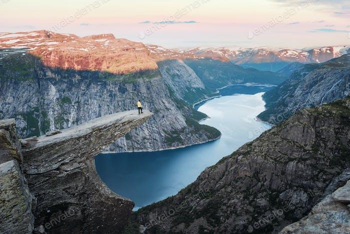 Tourist on Trolltunga rock in Norway mountains