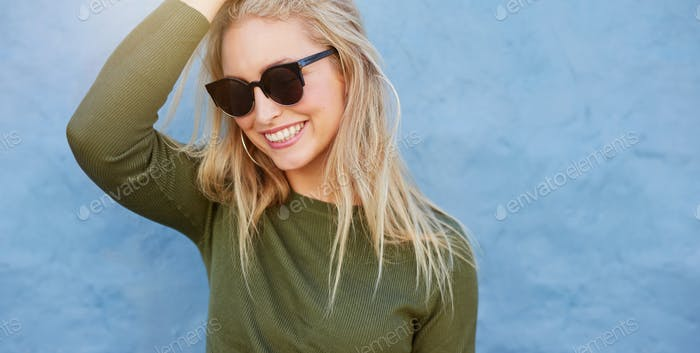 Cheerful young female model with sunglasses