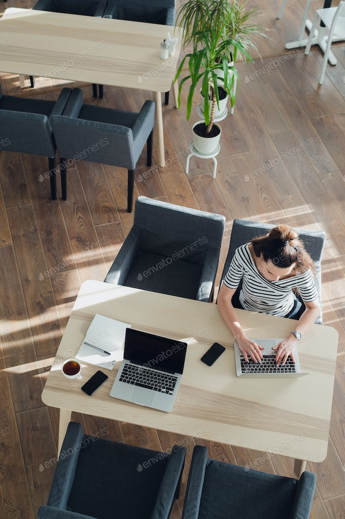 Overhead view or top view of a beautiful woman sitting at a table and working on her laptop. The sun