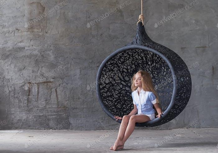 Cute female posing in swinging oval chair.