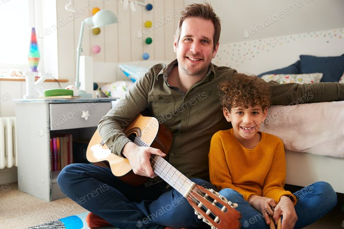 Portrait Of Single Father At Home With Son Playing Acoustic Guitar In Bedroom
