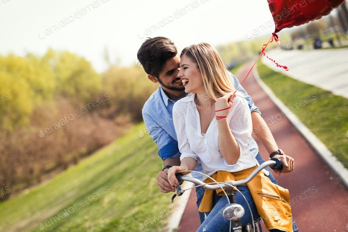 Young loving couple dating while riding bicycles in the city