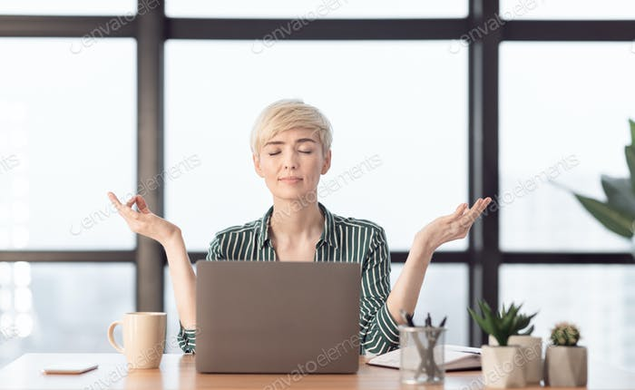 Mature Businesswoman Meditating Relaxing Sitting In Modern Office