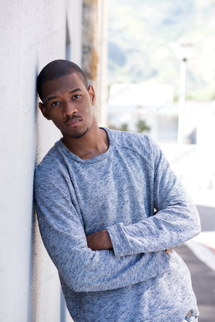 Portrait of young black man leaning against wall