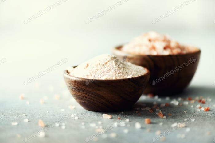 Pink Himalayan salt crystals and powder in wooden bowls on grey concrete background. Healthy diet