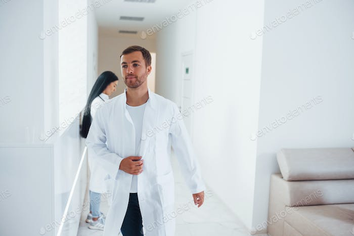 Doctor and brunette nurse in formal clothes that is in hospital