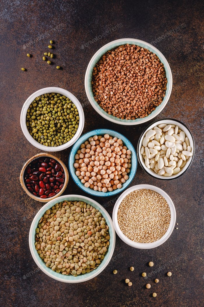 Top view on bowls with various raw grains and seeds on a textured dark background.