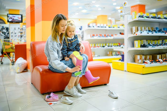 Mother and little daughter buys shoes, kid's store