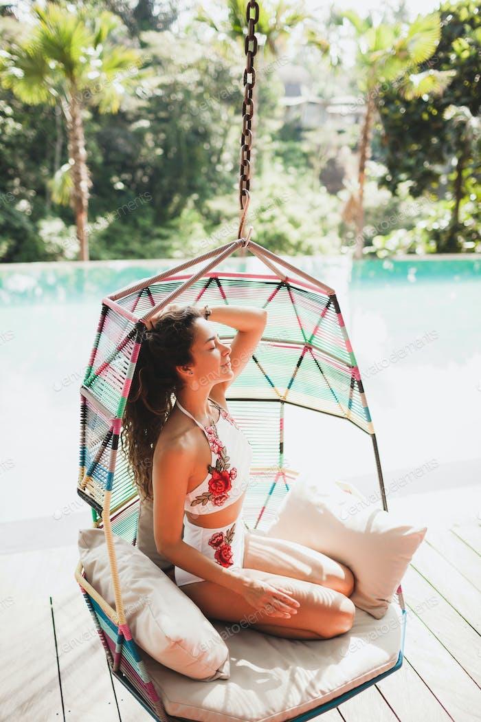 Woman in white swimsuit enjoying in hanging chair swing on poolside in luxury hotel