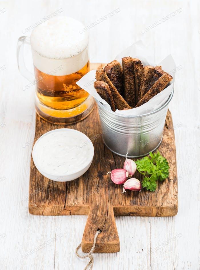 Pint Pilsener in Becher, offene Glasflasche, Roggenbrot Croutons