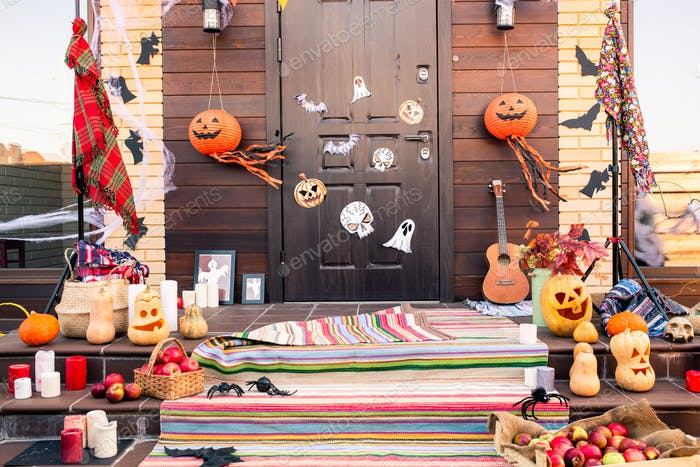 Door of country house decorated with halloween symbols in front of staircase