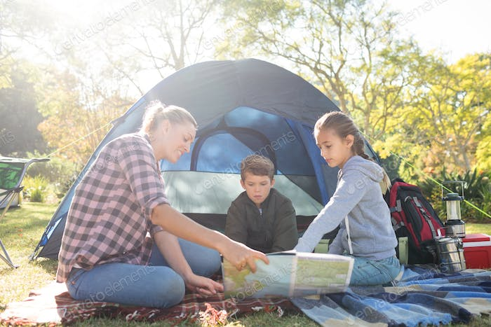 Family reading the map outside the tent