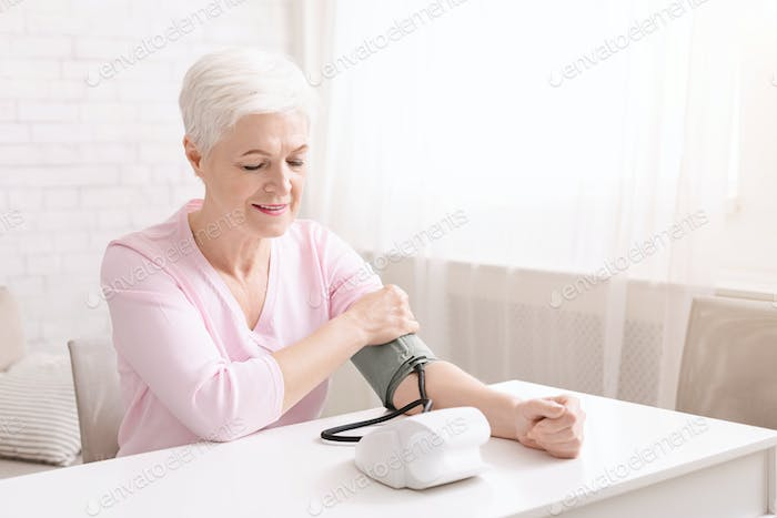 Senior lady with hypertension measuring blood pressure herself