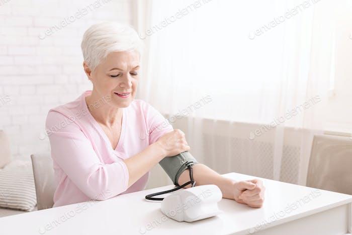 Senior Lady mit Bluthochdruck Messung des Blutdrucks selbst