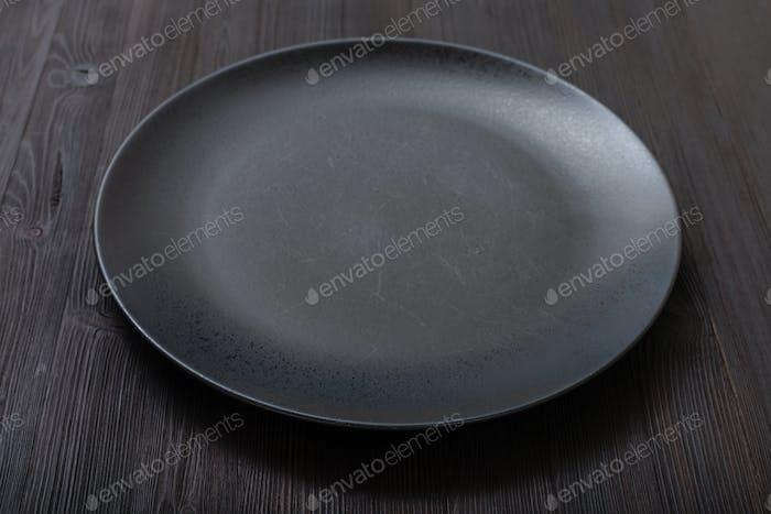 schwarzer Teller auf dunkelbraunem Tisch