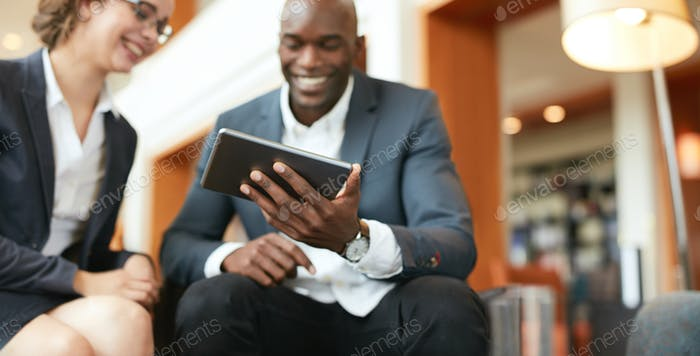 Business people using digital tablet at hotel lobby