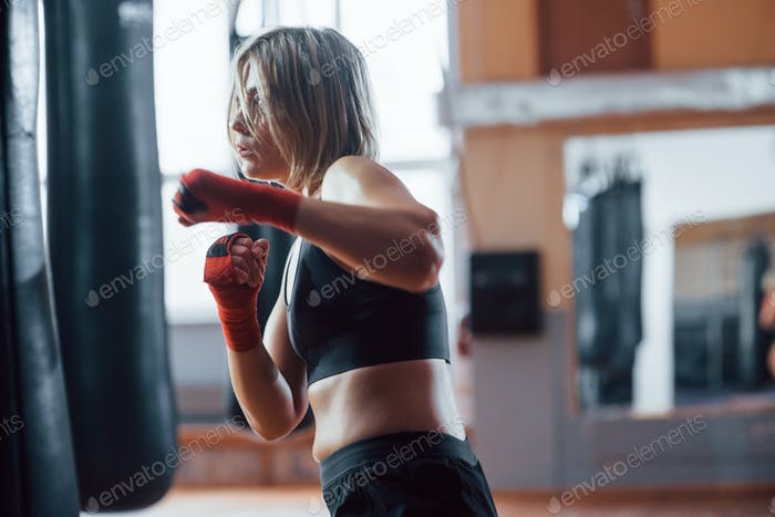Aggressive kick. Female boxer is punching the bag. Blonde have exercise in the gym