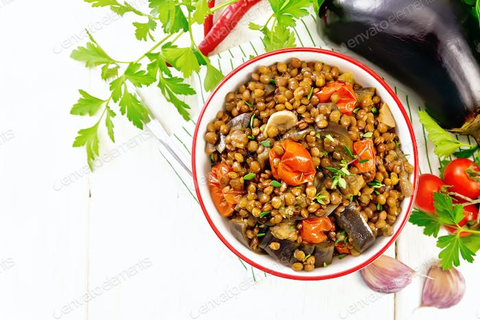 Lentils with eggplant in bowl on board top