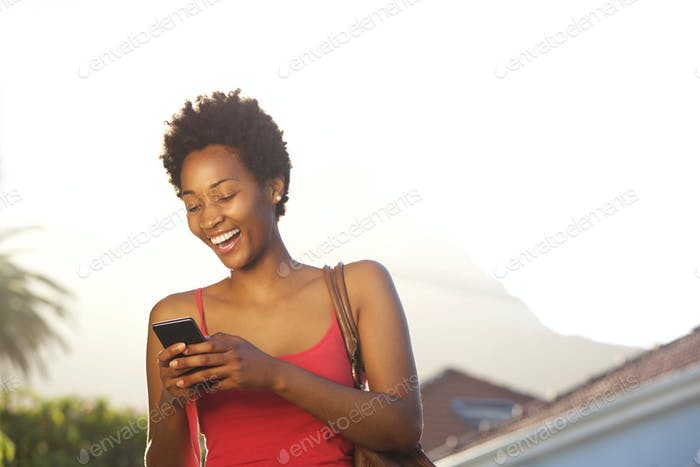 Smiling young african reading text message on her mobile phone