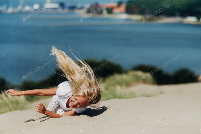 a child has fun in the sand dunes on the beach in Nida.Lithuania