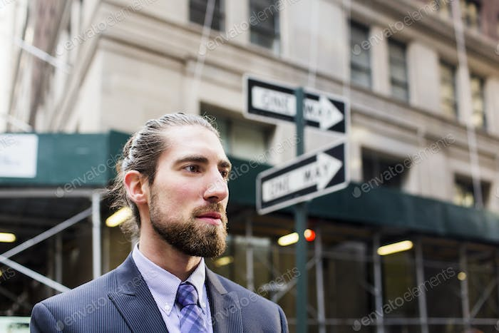 Close-up of young businessman standing against buildings in city