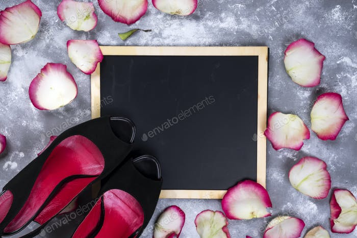 Beautiful rose flowers and woman shoes on gray stone table. Floral border.
