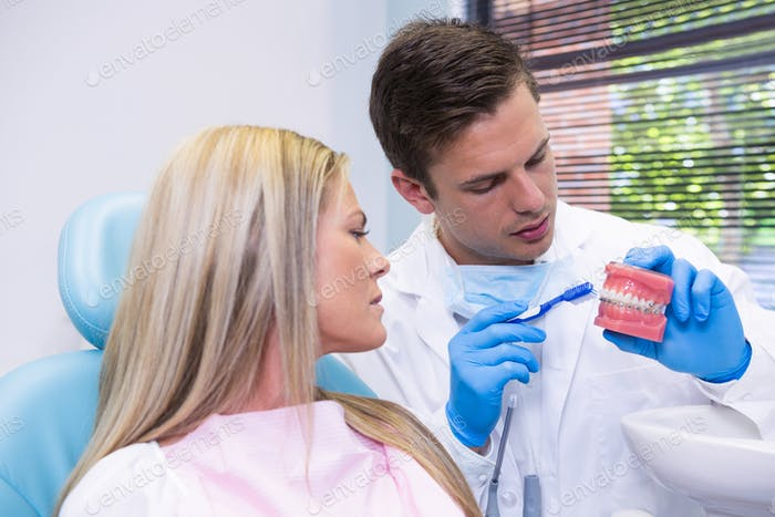 Dentist showing dental mold to woman