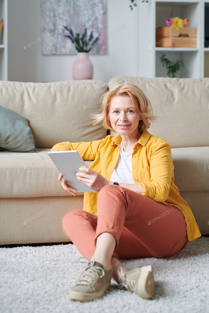 Pretty mature woman with digital tablet relaxing on the floor by couch at home