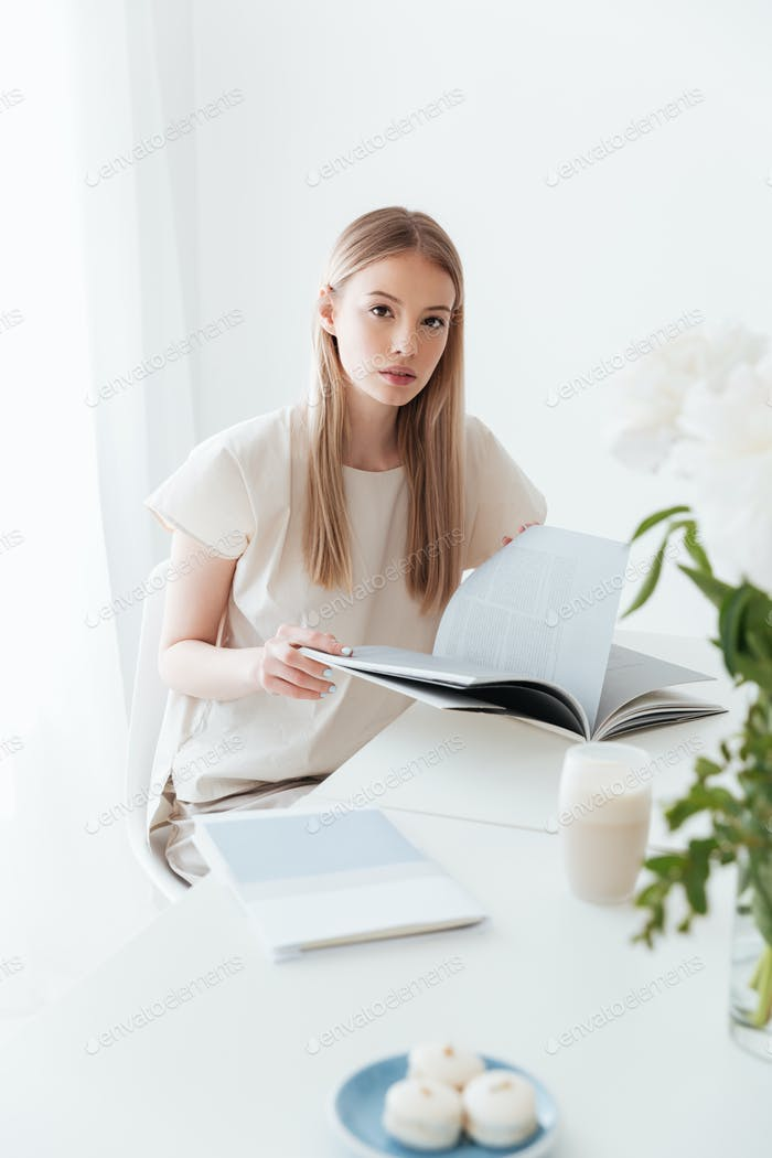 Woman sitting indoors reading book. Looking at camera.