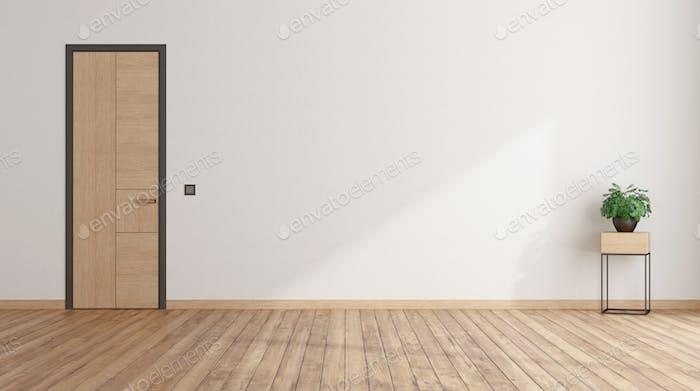 Leeres Zimmer mit geschlossener Tür und Zimmerpflanze