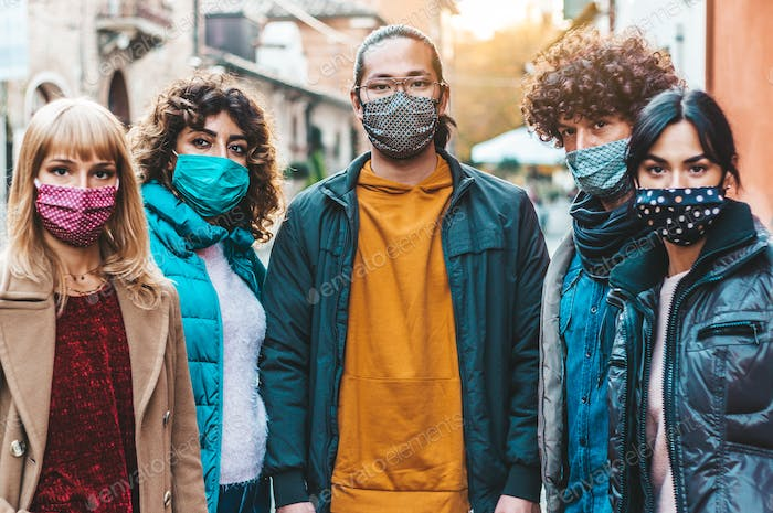 Urban crowd of citizens in city street covered by face mask looking at camera