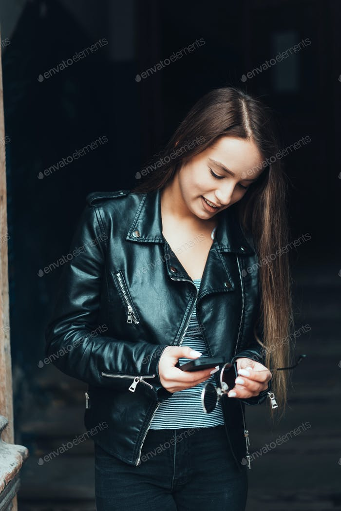 Beautiful girl in black jacket with smartphone