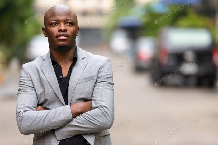 Happy young handsome bald African businessman thinking outdoors