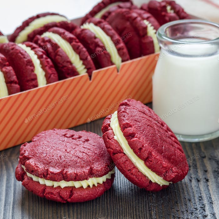 Red velvet sandwich cookies with cream cheese filling on wooden table, square format