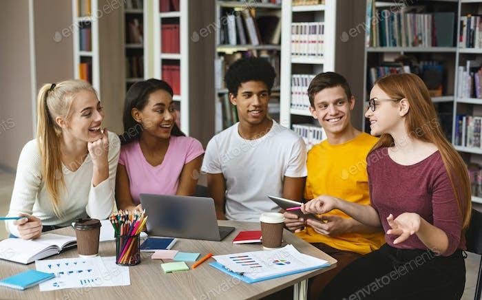 Группа многоэтнических подростков, делающих домашнее задание в библиотеке
