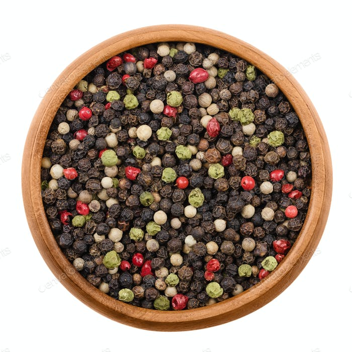 Mixed peppercorns in a wooden bowl over white