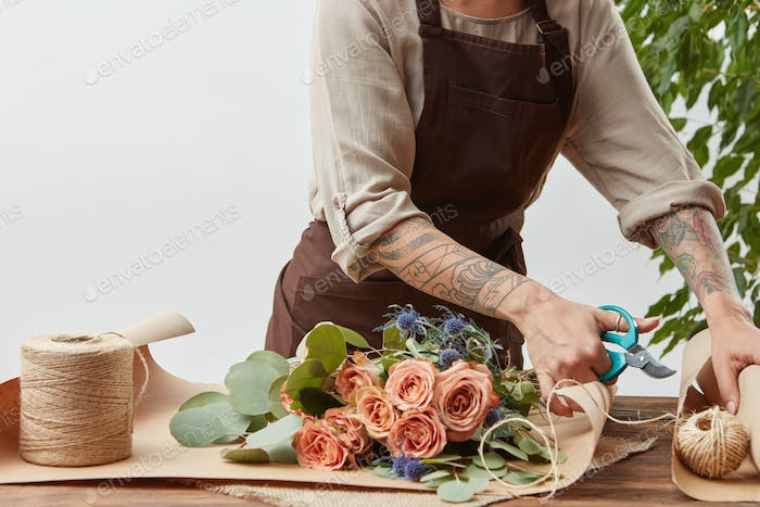 Female florist is cutting paper for creating beautiful bouquet on a background of light wall. Place