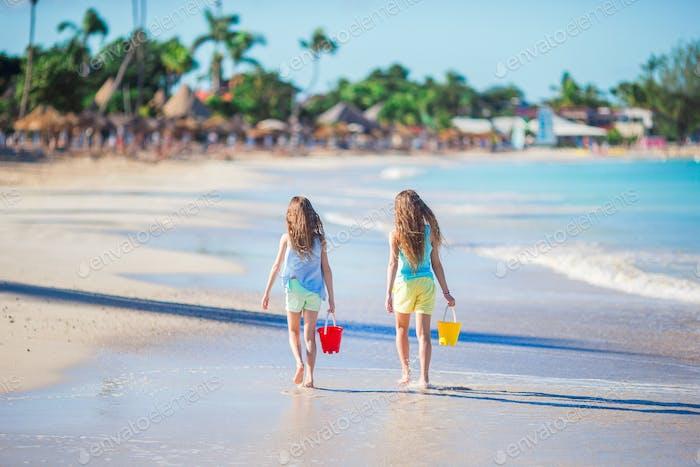 Rear view of little beautiful girls walking on tropical seashore