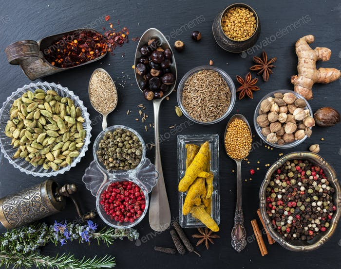 Variety of colorful spices and herbs on black stone background, top view