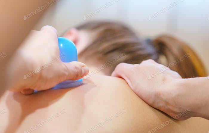 Hands of massage therapist and silicone massage jar on the back of girl