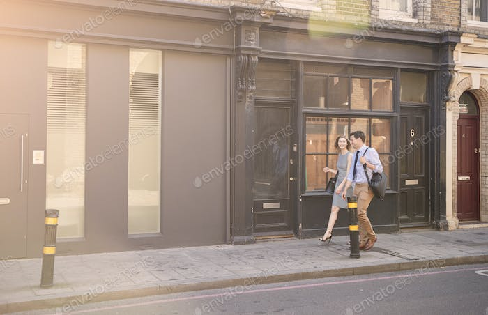Businessman And Businesswoman Walk to Work Through City Street